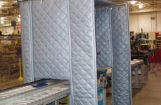 Quilted industrial noise control curtain in a manufacturing facility.