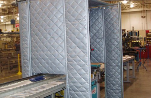 Quilted industrial sound blanket enclosure in a manufacturing facility.